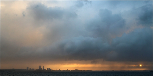 A storm passing over Perth as the sun rises over the hills